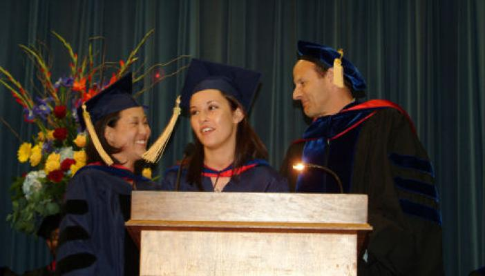 Photo of people standing at podium during Graduation