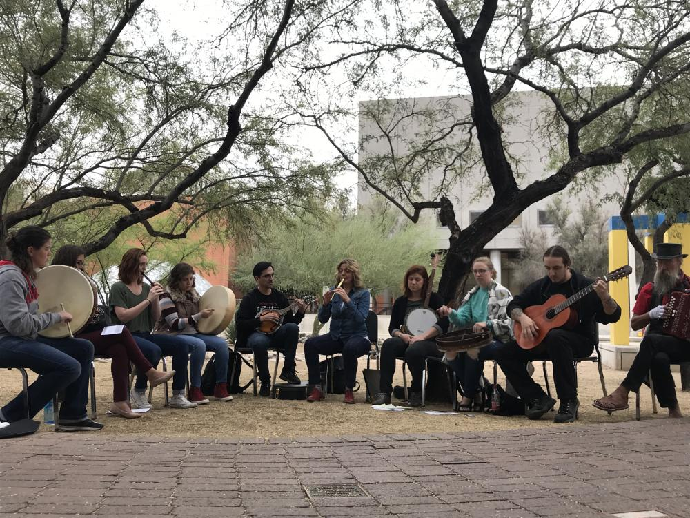 Photo of people sitting in a semi-circle playing musical instruments